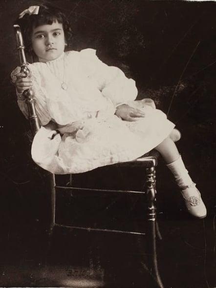 Frida Kahlo de niña sentada en una silla