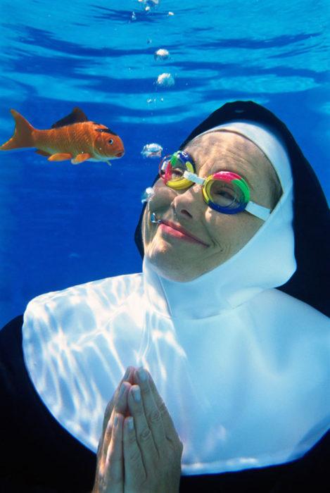 Imágenes incomprensibles - monja abajo del agua con googles mientra ve un pez