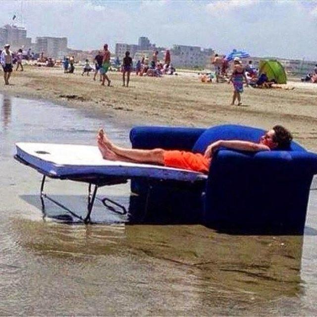 chavo sentado en la playa en un sofá cama