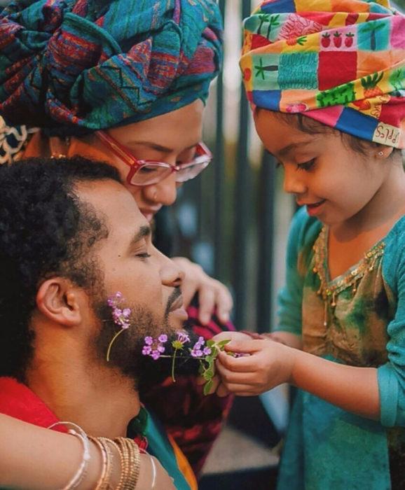 niña decorando con flores la barba de su papá
