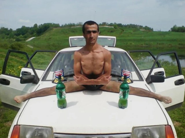 hombre con las piernas abiertas encima d eun auto blanco