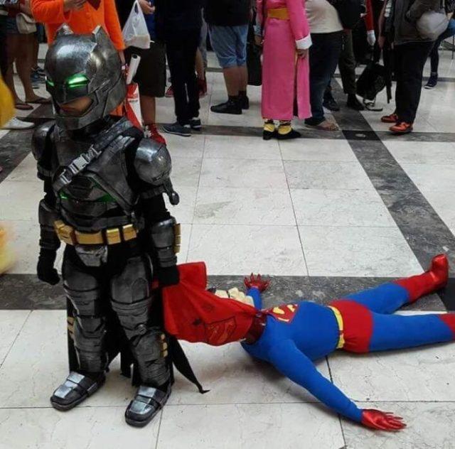 Niño disfrazado de Batman arrastrando a Spiderman