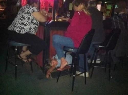 Mujer en el bar mientras su hijo duerme en el piso