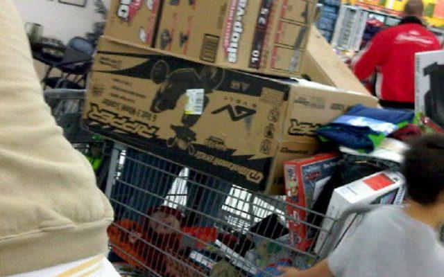 Niño dormido en carrito de compras y arriba va repleto de cajas