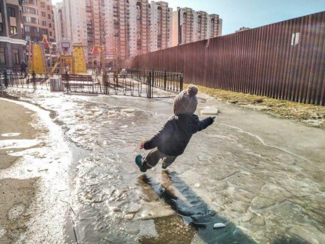 niño a punto de caer por suelo resbaloso por hielo