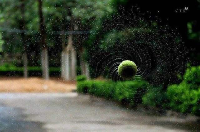 Pelota de tenis girando sacando el agua acumulada