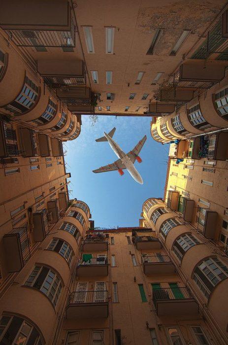 momento justo que aeroplano pasa ente edificio