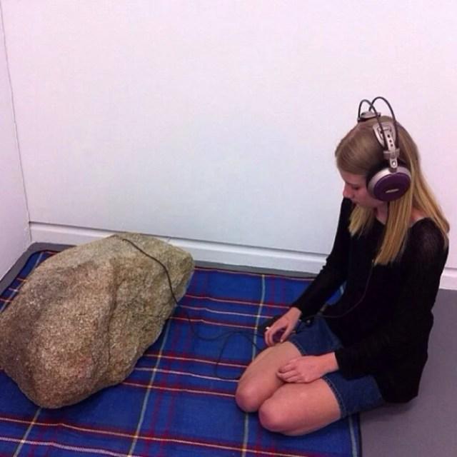 chica con una gran roca y audífonos