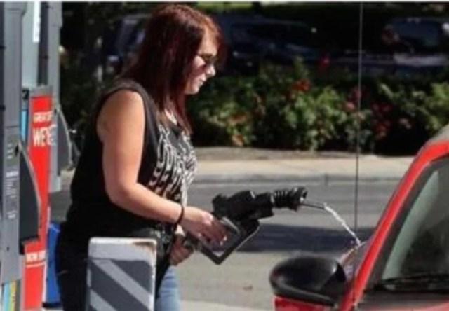 mujer en estación de gasolina haciéndolo mal