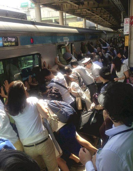Personas empujando el metro