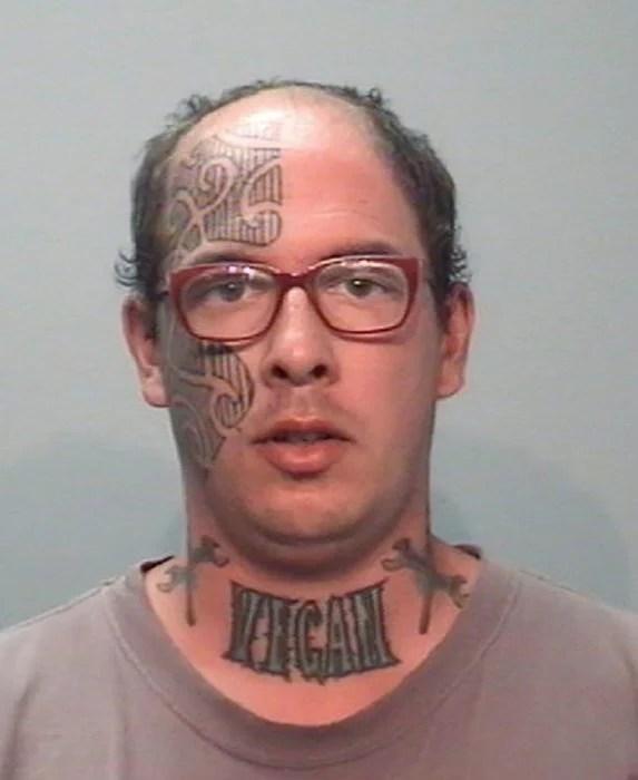 Hombre con media cara tatuada y el cuello dice que es vegano