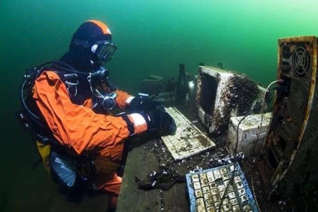 buzo dentro del agua con computadora