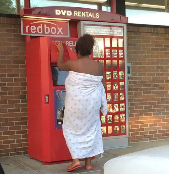 mujer cubierta por cobijas rentando una película