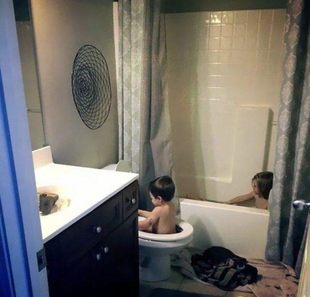 Niño bebiendo el baño en el escusado
