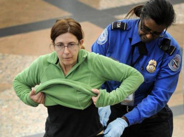 mujer en un aeropuerto siendo cacheada