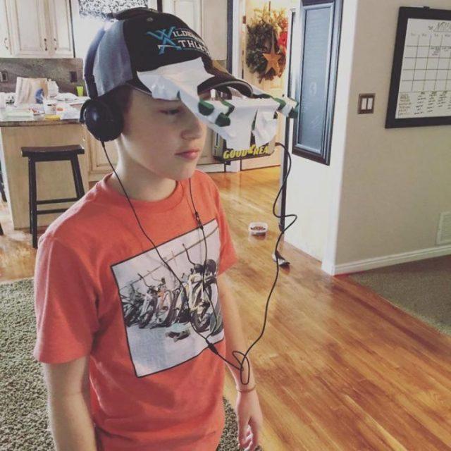Niño con celular en la gorra