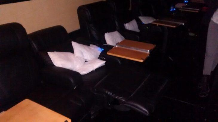 asiento con mesitas y almohadas en el cine