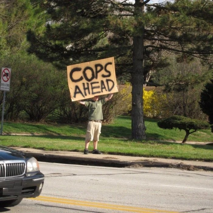 hombre con un cartel que advierte sobre policías