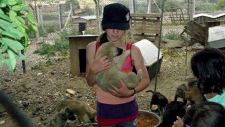 niña cargando un cachorro