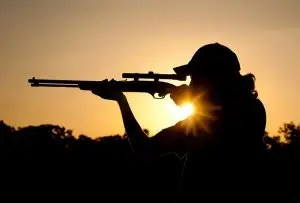 silhouette of a young man shooting with a long rifle