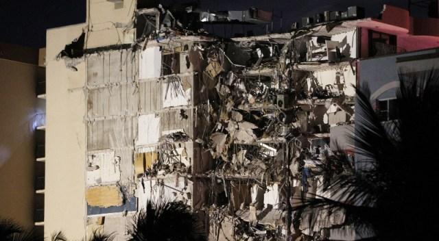 Dos torres de edificios, una de las cuales se muestra parcialmente derrumbada.