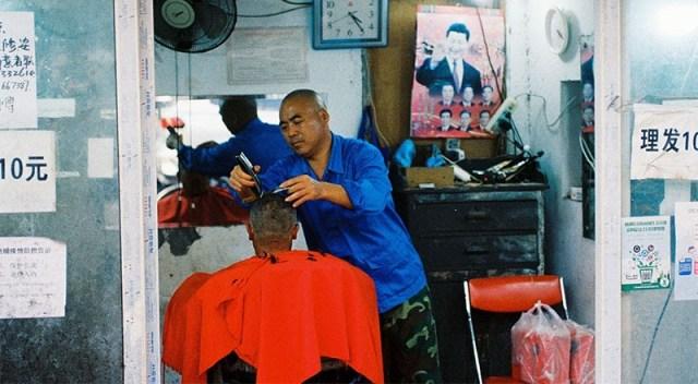 Foto de un peluquero que corta el cabello en China.