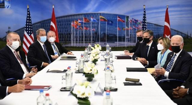 Líderes de la OTAN reunidos alededor de una mesa, con banderas de fondo.