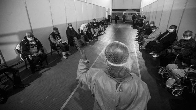 Personas en situación de calle en la pandemia en una habitación escuchan las indicaciones de un trabajador de salud.