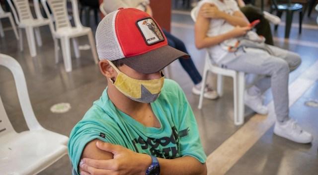 Chico con gorra se toma el brazo tras recibir vacuna.