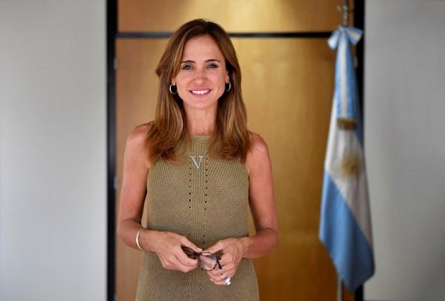 Mujer parada mira de frente, con la bandera argentina en un mástil en el fondo.