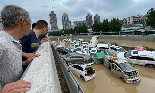 Personas miran desde un puente autos que flotan en medio de una inundación.
