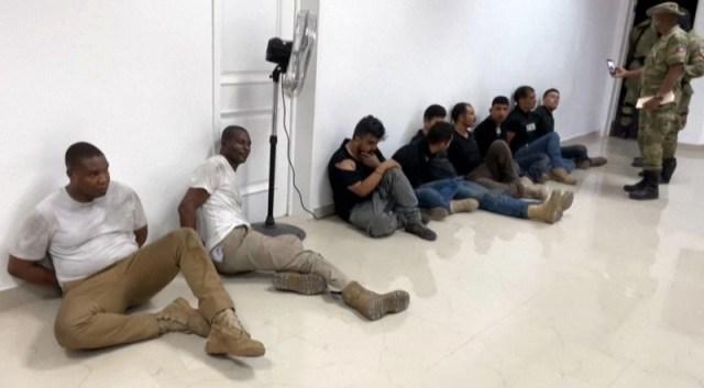 Ocho sospechosos sentados en el suelo, custodiados por dos policías.