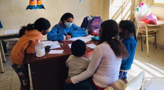 Una trabajadora de la salud escribe en su escritorio rodeada de adultos y niños de una comunidad rural de Santiago del Estero.