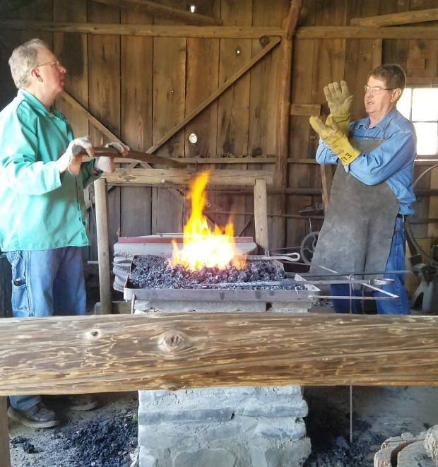 Julie Zeeb - Daily NewsNoble Engle, right, talks about how the bellows work to control the size of the flame in the forge on Saturday during a blacksmith workship held at William B. Ide Adobe State Historic Park.