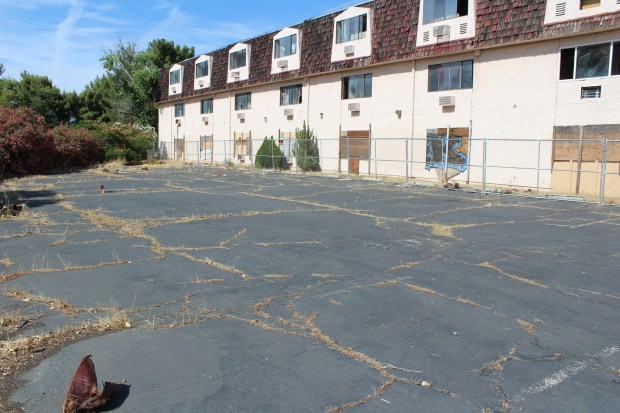 The parking lot near the abandoned hotel on Sutter Street where a fence surrounds the building and cracks have given way to weed growth. (Jake Hutchison - Daily News)