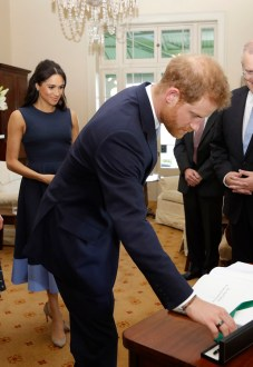 Prince Harry, Duke of Sussex signs a visitors book as he and Meghan, Duchess of Sussex at Kirribilli House