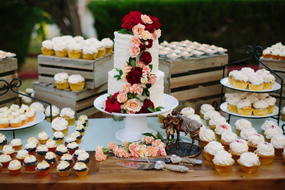 A rustic dessert display that enhances the experience. This display features cake, cupcakes, and flowers.