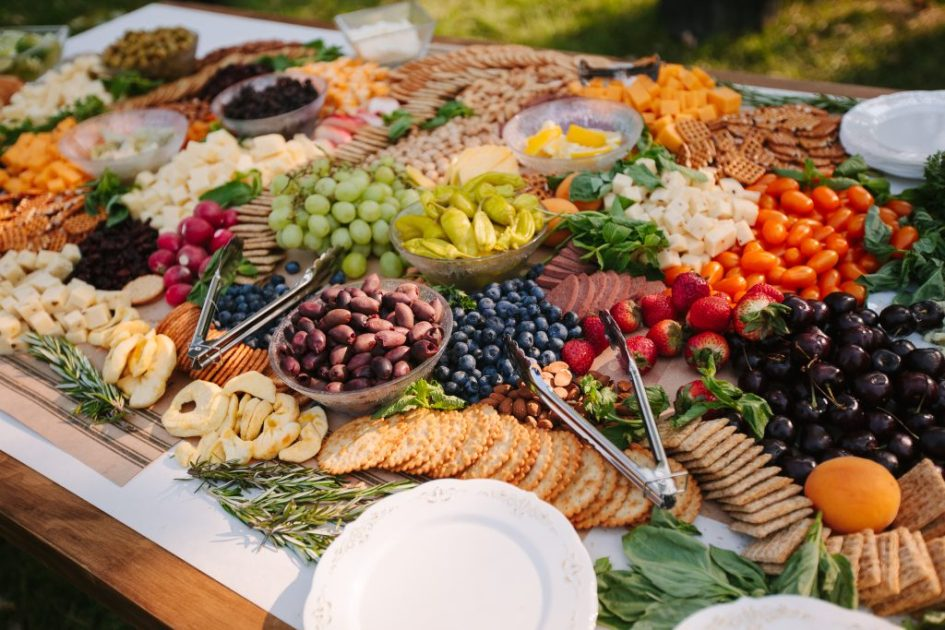 Image of cheese, fruit, and crackers on a large wooden farm table.