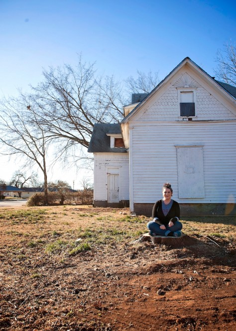 Our photographer, Rachel J Apple, sitting outside an old home in Stillwater, OK.