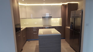 kitchen remodelling fitout dubai, modern kitchen executive towers, business bay kitchen, stone counters, island kitchen, corner storage, built in washing machine