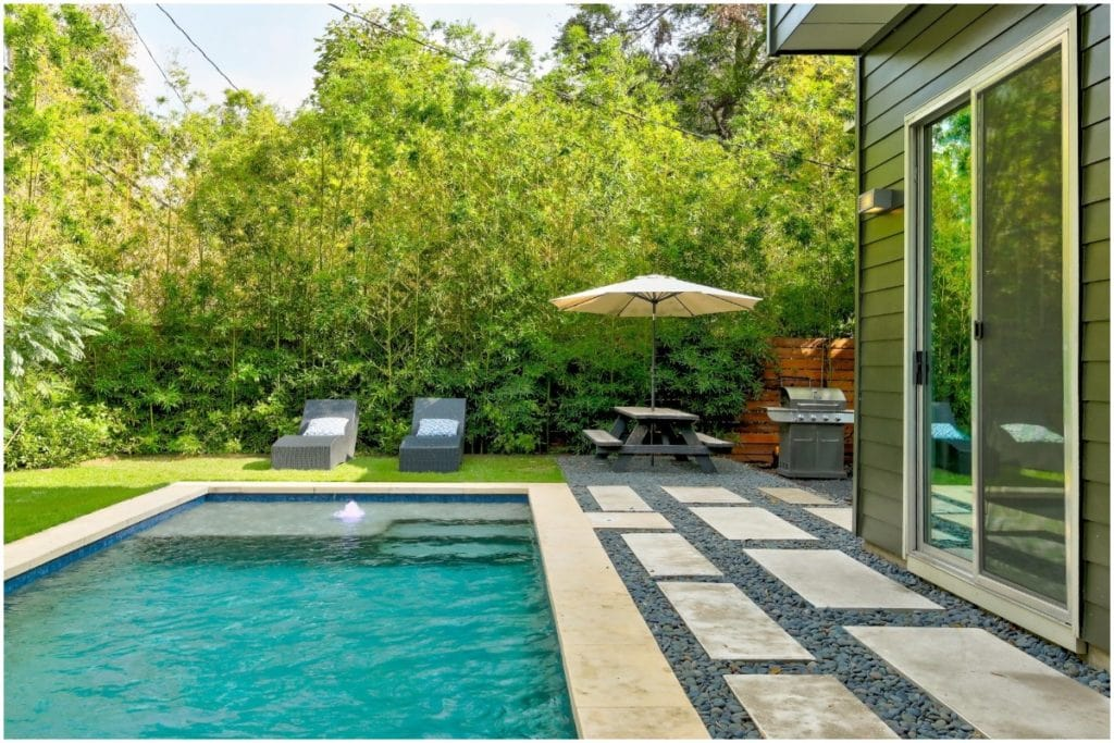 backyard with large trees and blue pool