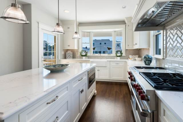 A clean kitchen with stainless steel appliances, white cabinets, and white quartz countertops