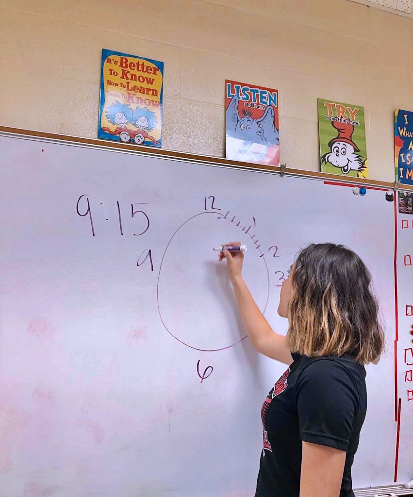 kenia writing on the board with a marker teaching about the numbers on a clock  author: maidelyn perales