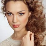 Strawberry blonde curly hairstyle with french crown braid