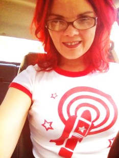JoEllen sitting in a car wearing brown glasses and a white t-shirt with red rings on the sleeves and neck and a red vibrator design on the front