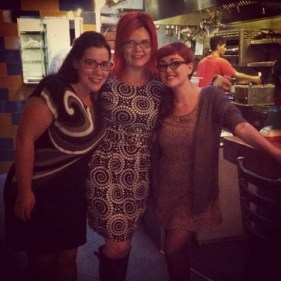 Three women - one brunette and two redheads- standing together in a restaurant.
