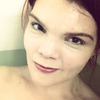 JoEllen visible from shoulders up smiling in white bath tub