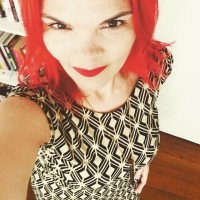 JoEllen with exceptionally red hair and lipstick taking a selfie in a black and white dress