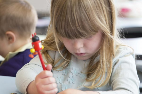 Close-up photograph of a young girl drawing on paper in a room at The Red Hen Project.