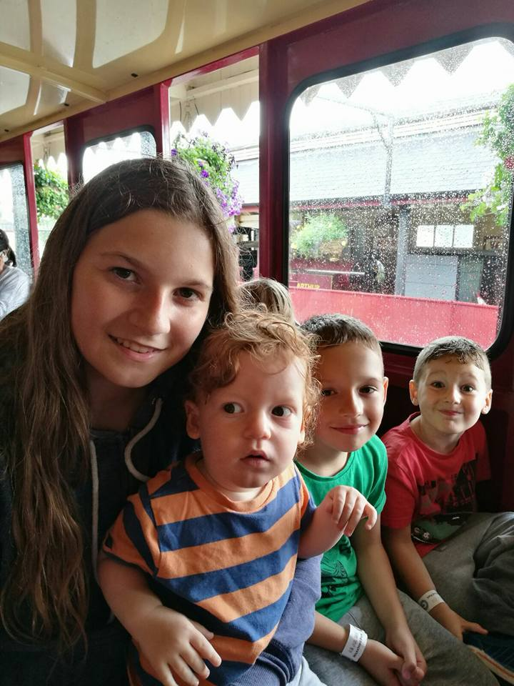 Photograph of Julie and three of her young children on a train.